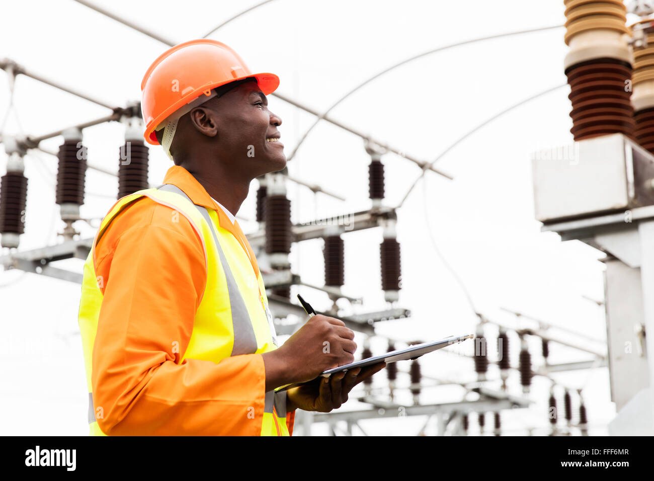 male African electrical worker in substation - Stock Image