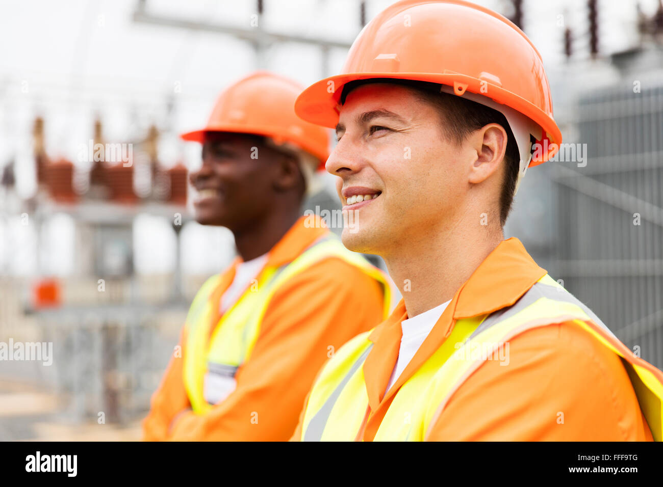 handsome electrical engineer looking away with colleague on background - Stock Image