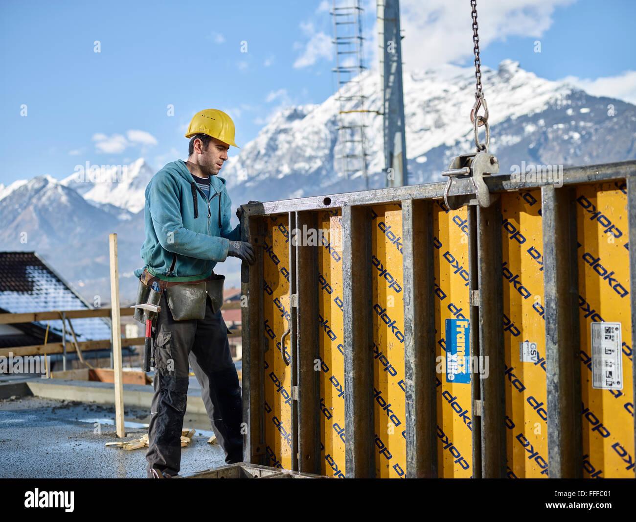 Construction worker lifting shuttering wall with crane, preparing framed formwork, Kolsass, Innsbruck Land, Tyrol, - Stock Image