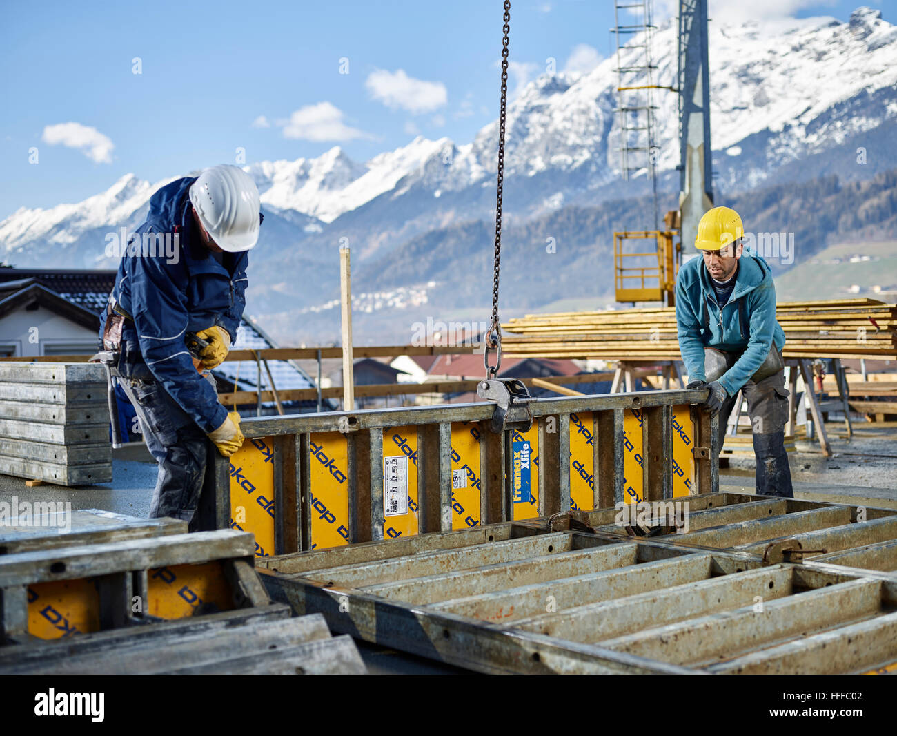 Construction workers lifting shuttering wall with crane, preparing framed formwork, Innsbruck Land, Tyrol, Austria - Stock Image