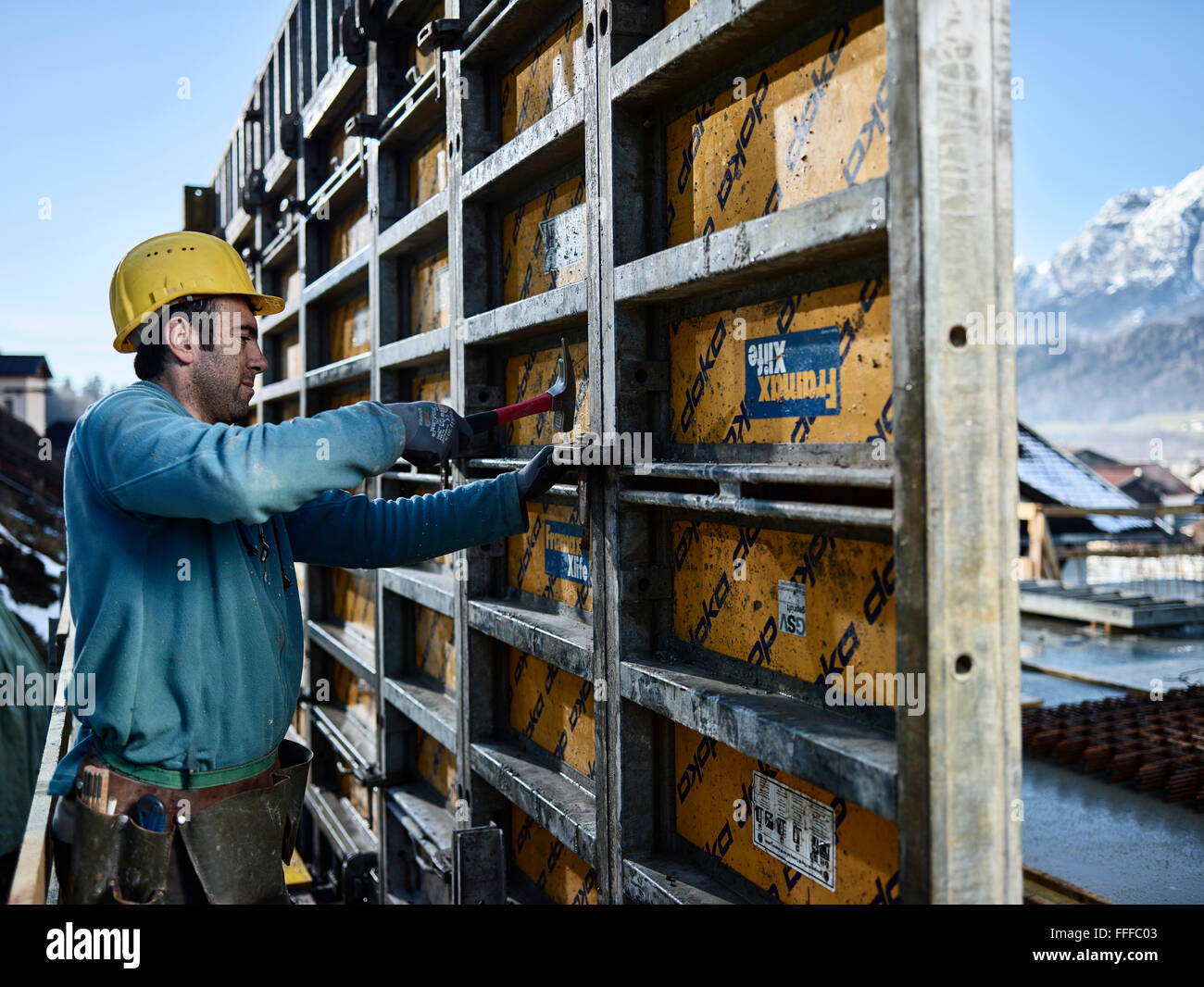 Construction worker hitting connecting element with hammer, shuttering wall, Innsbruck Land, Tyrol, Austria - Stock Image