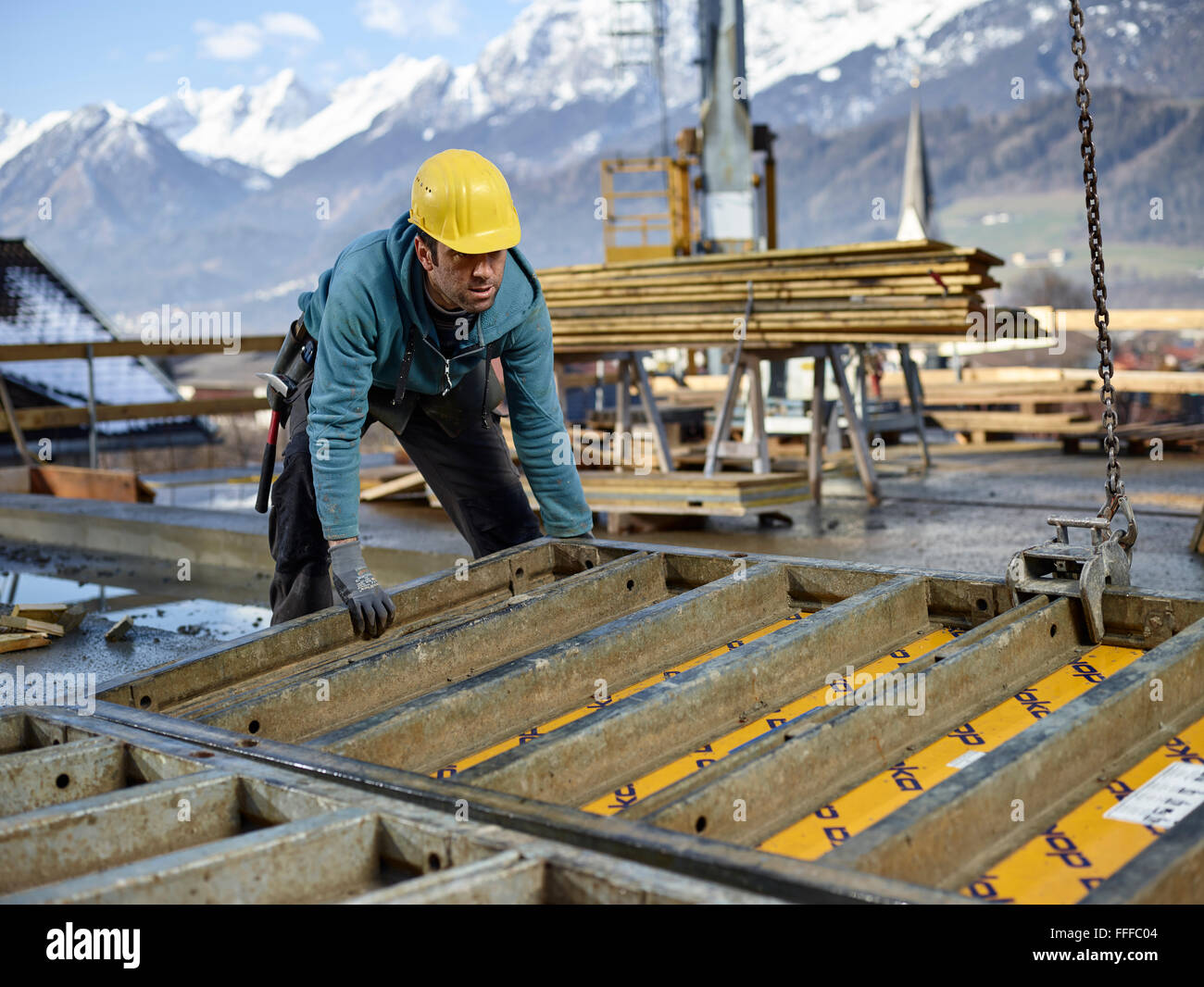 Construction worker lifting shuttering wall with crane, preparing framed formwork, Innsbruck Land, Tyrol, Austria - Stock Image