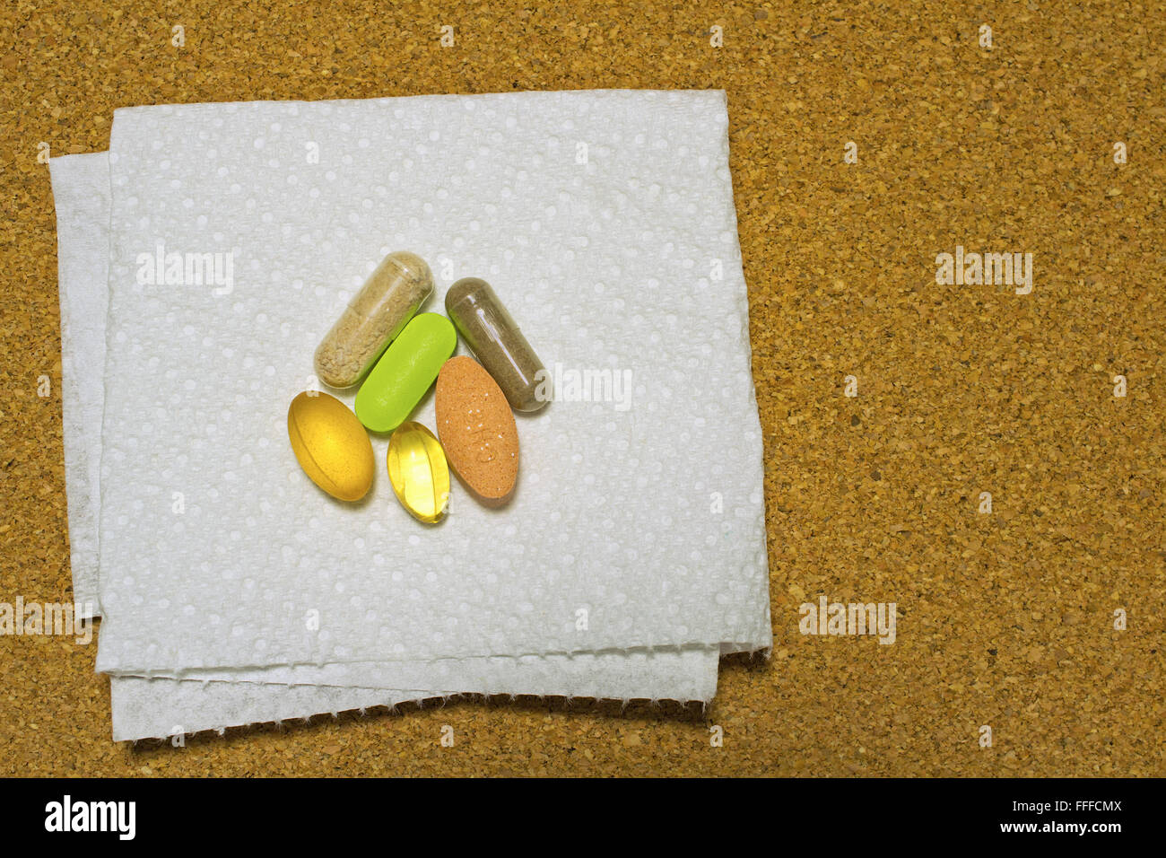 Dietary supplements on paper towel over cork background - Stock Image