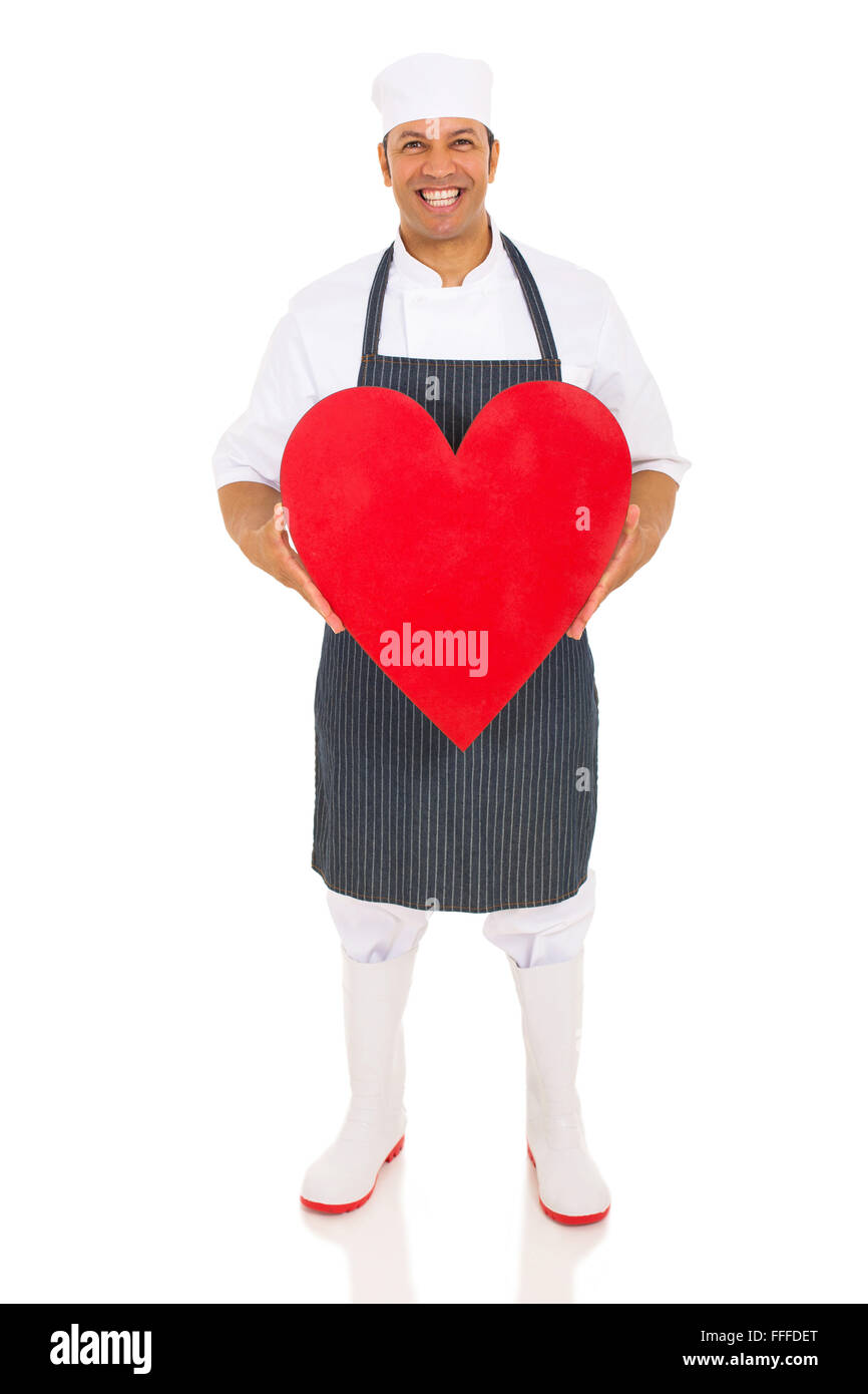 portrait of mid age butcher holding heart isolated on white - Stock Image