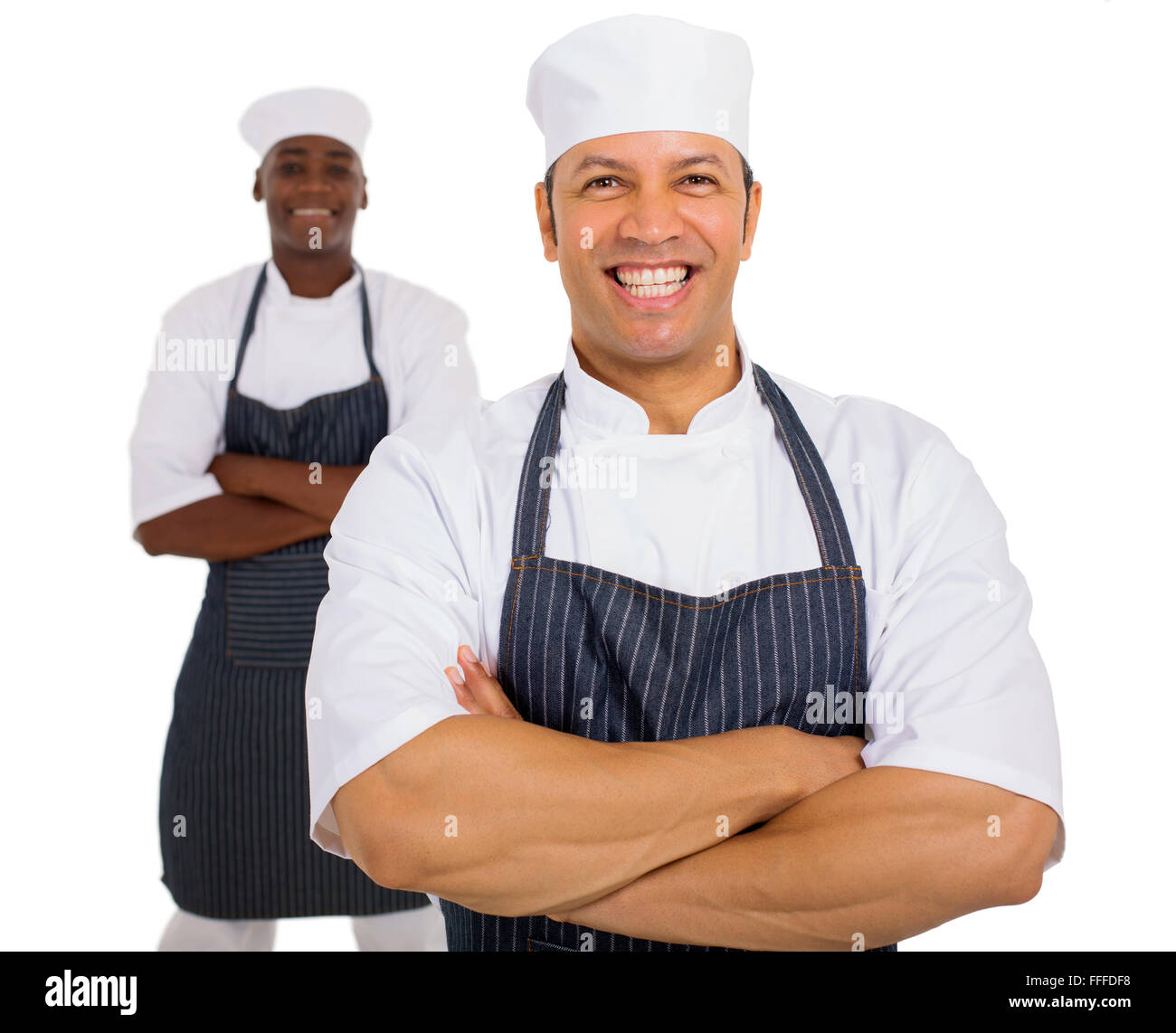 portrait of mid age chef with co-worker on background - Stock Image
