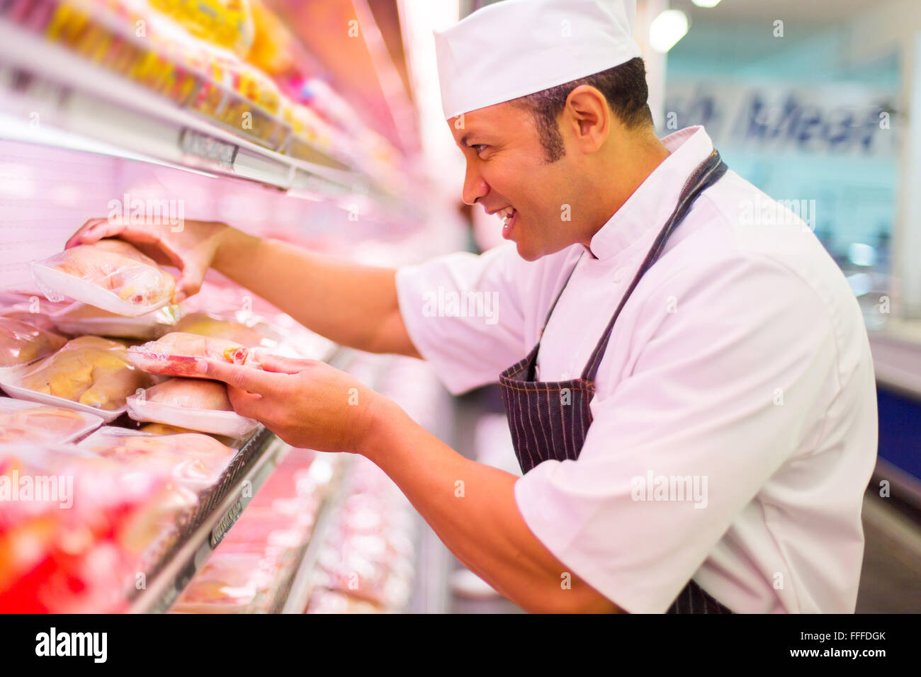 happy middle aged butcher working in butchery - Stock Image