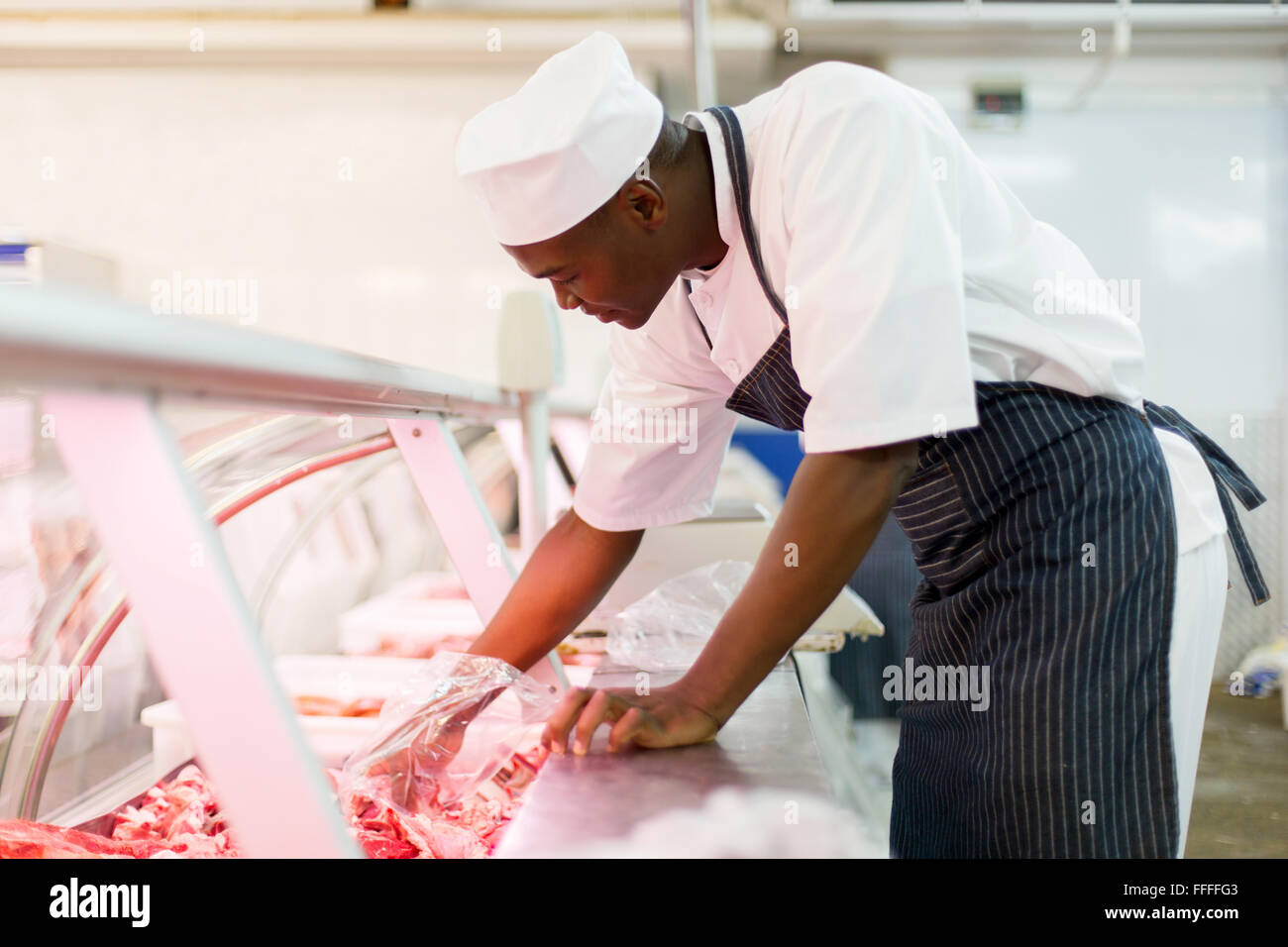 young African American butcher picking pieces of meat  in butchery - Stock Image