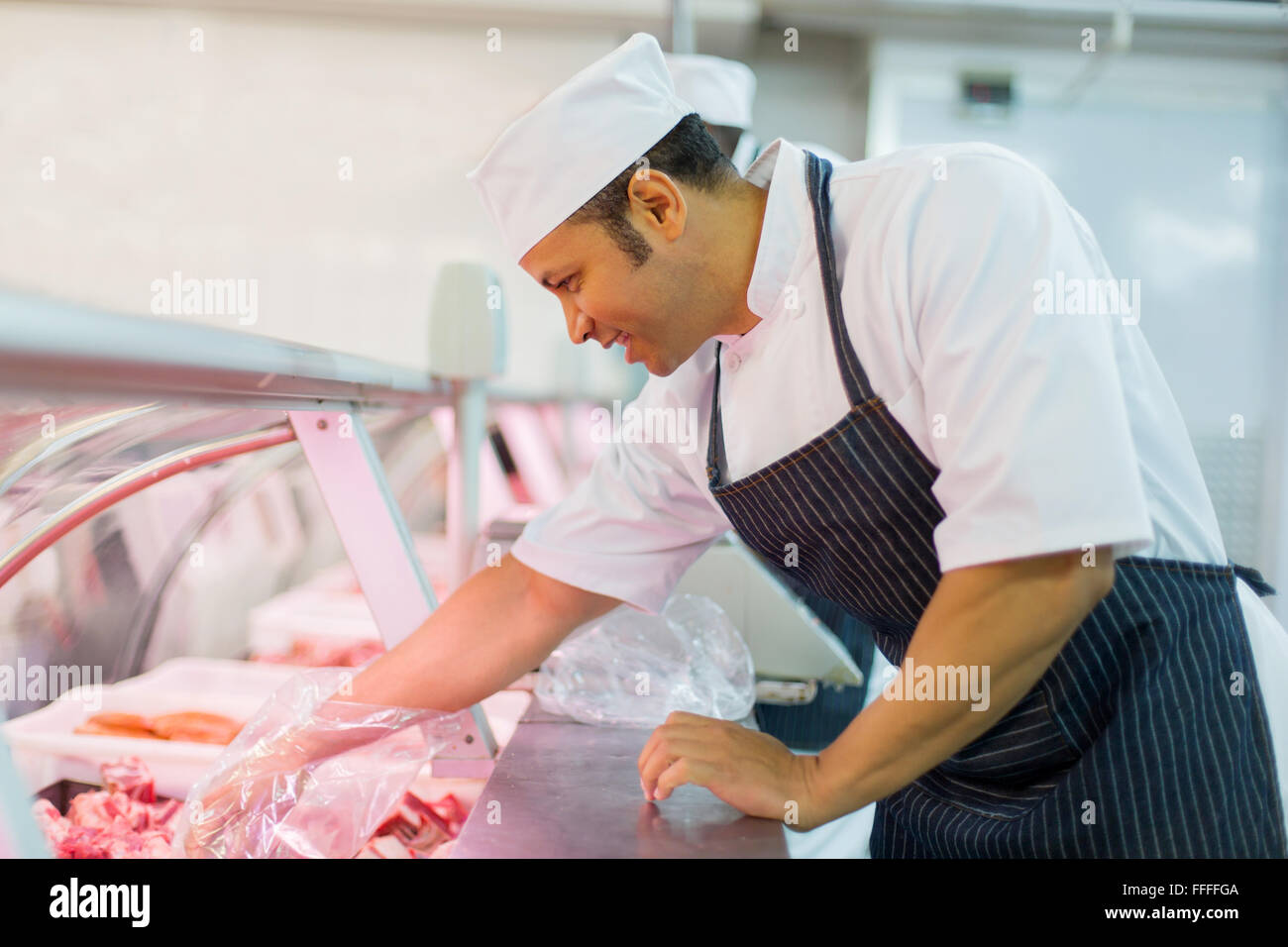 good looking butcher picking piece of meat Stock Photo