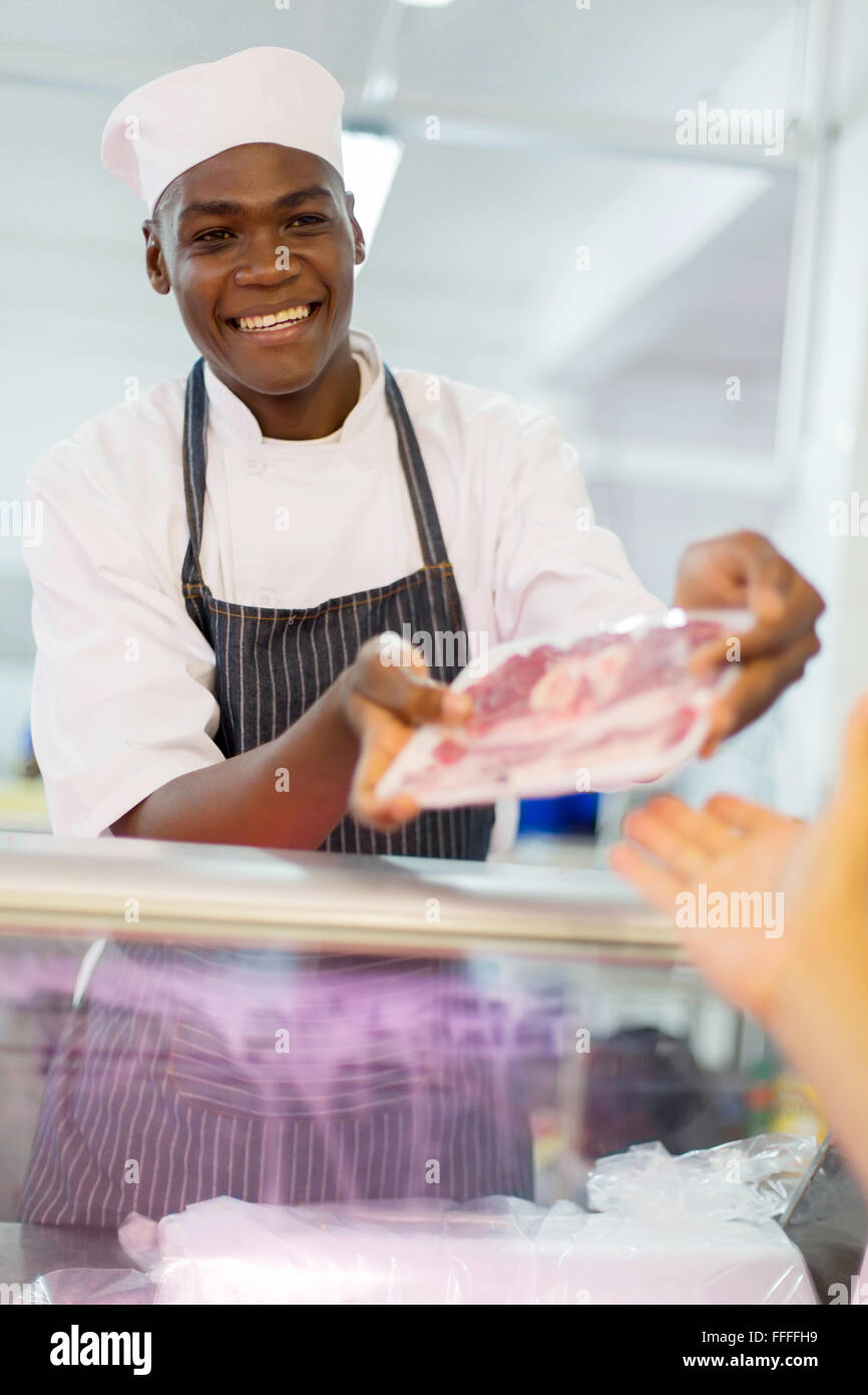 African butcher selling packed meat to customer in butchery - Stock Image