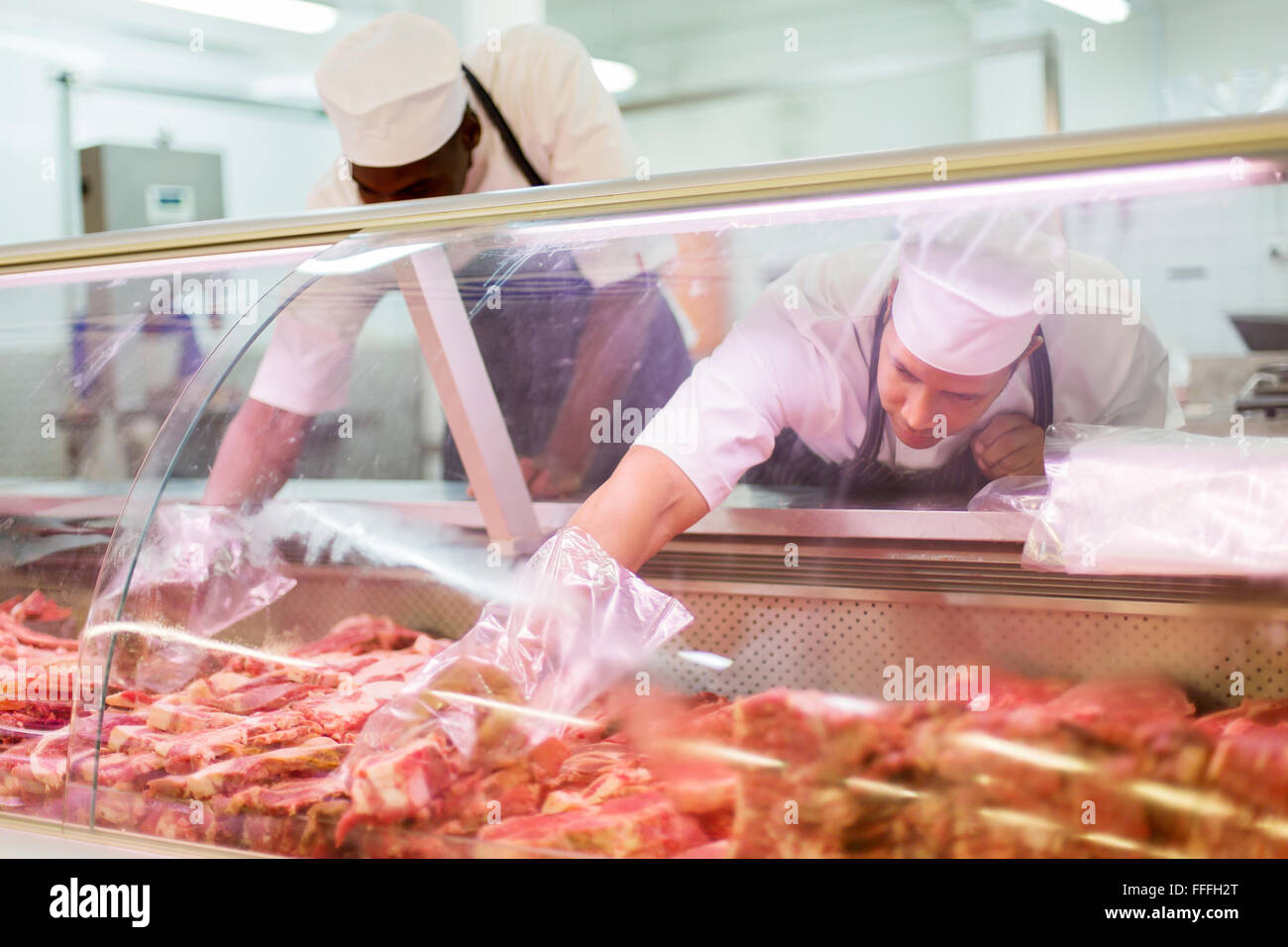 two butchers working in butchery - Stock Image