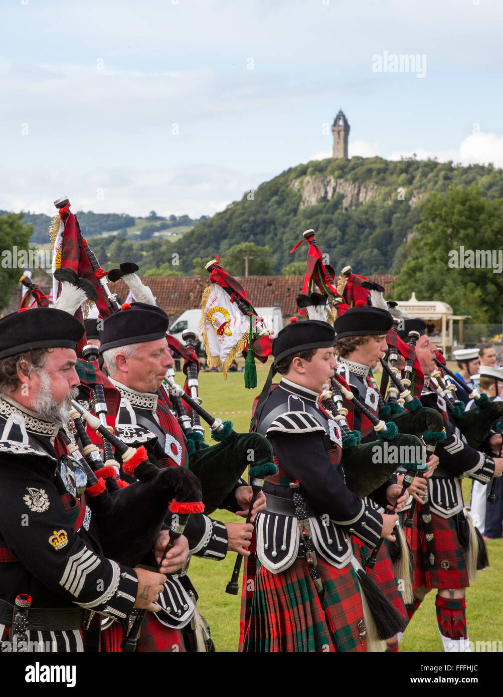 Scottish pipers playing bagpipes at the Stirling Highland games The National Wallace Monument, Stirling in Scotland Stock Photo