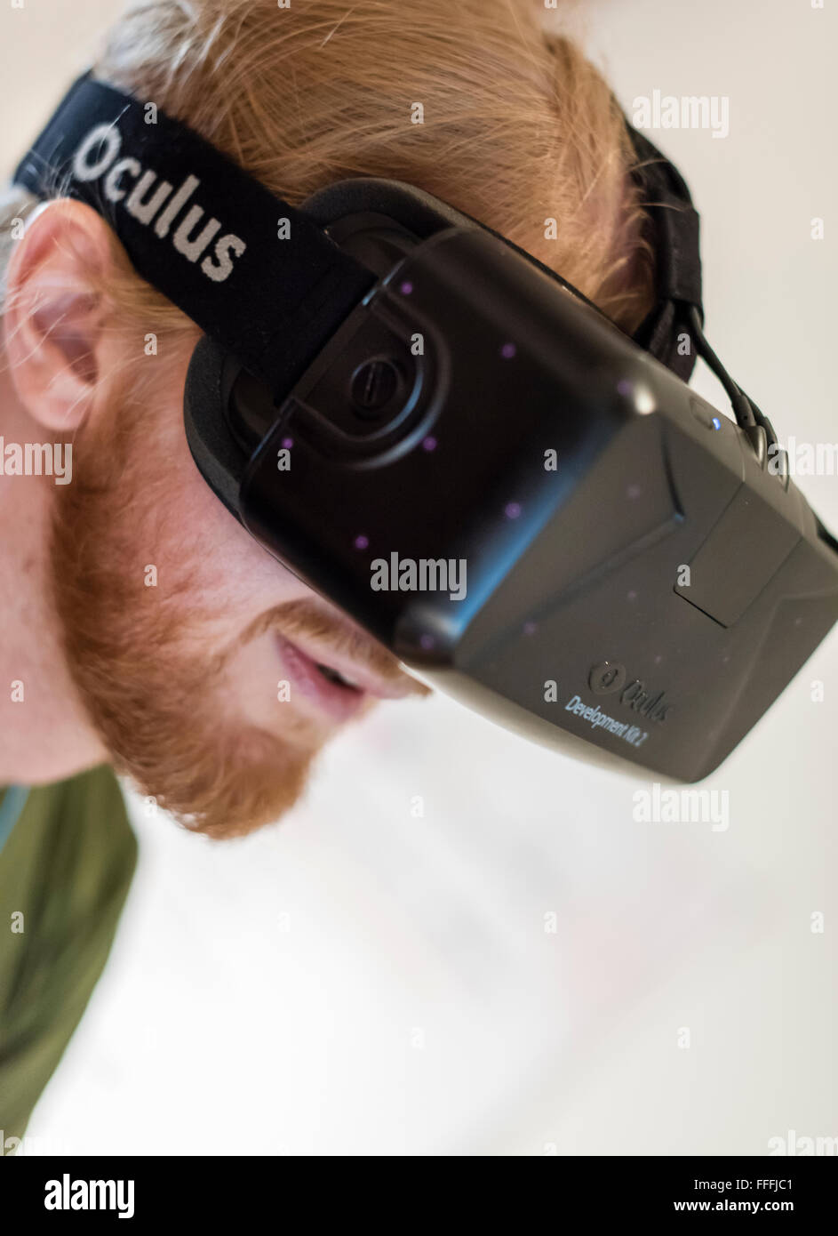A man (Caucasian ethnicity) is wearing Oculus Rift Development Kit 2 (DK2) virtual reality goggles while playing - Stock Image