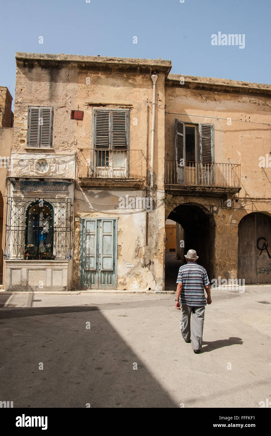 Old Italian man walking among decrepit houses in the medieval district  of Marsala, Sicily, Italy. - Stock Image