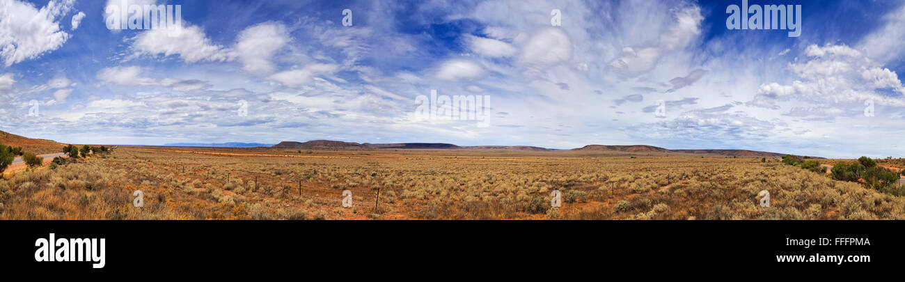wide 180 degrees panorama of endless plains in Australian outback on a summer sunny day. Fenced highway with flat - Stock Image