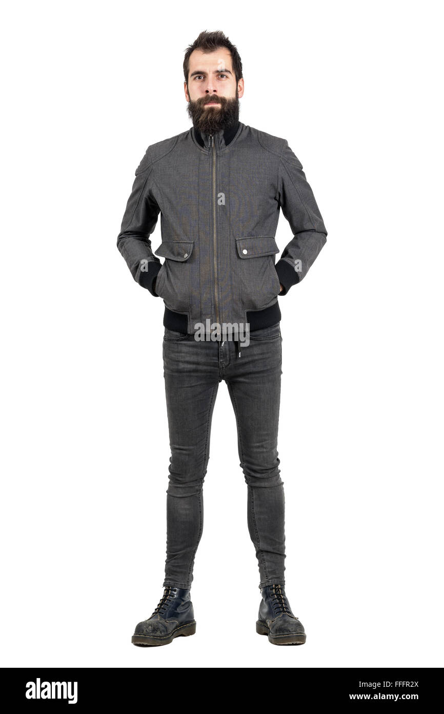 Confident bearded hipster in gray jacket, tight jeans and boots looking at camera. Full body length portrait isolated - Stock Image