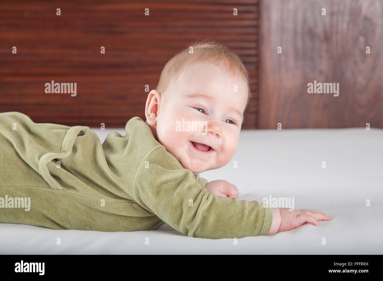 six months age blonde baby green velvet onesie lying on white sheet bed with brown wood background smiling happy Stock Photo