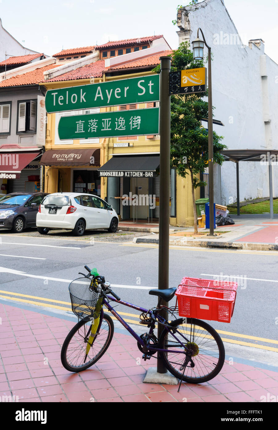 Bicycle leaning against a street sign for Telok Ayer St, Chinatown, Singapore - Stock Image