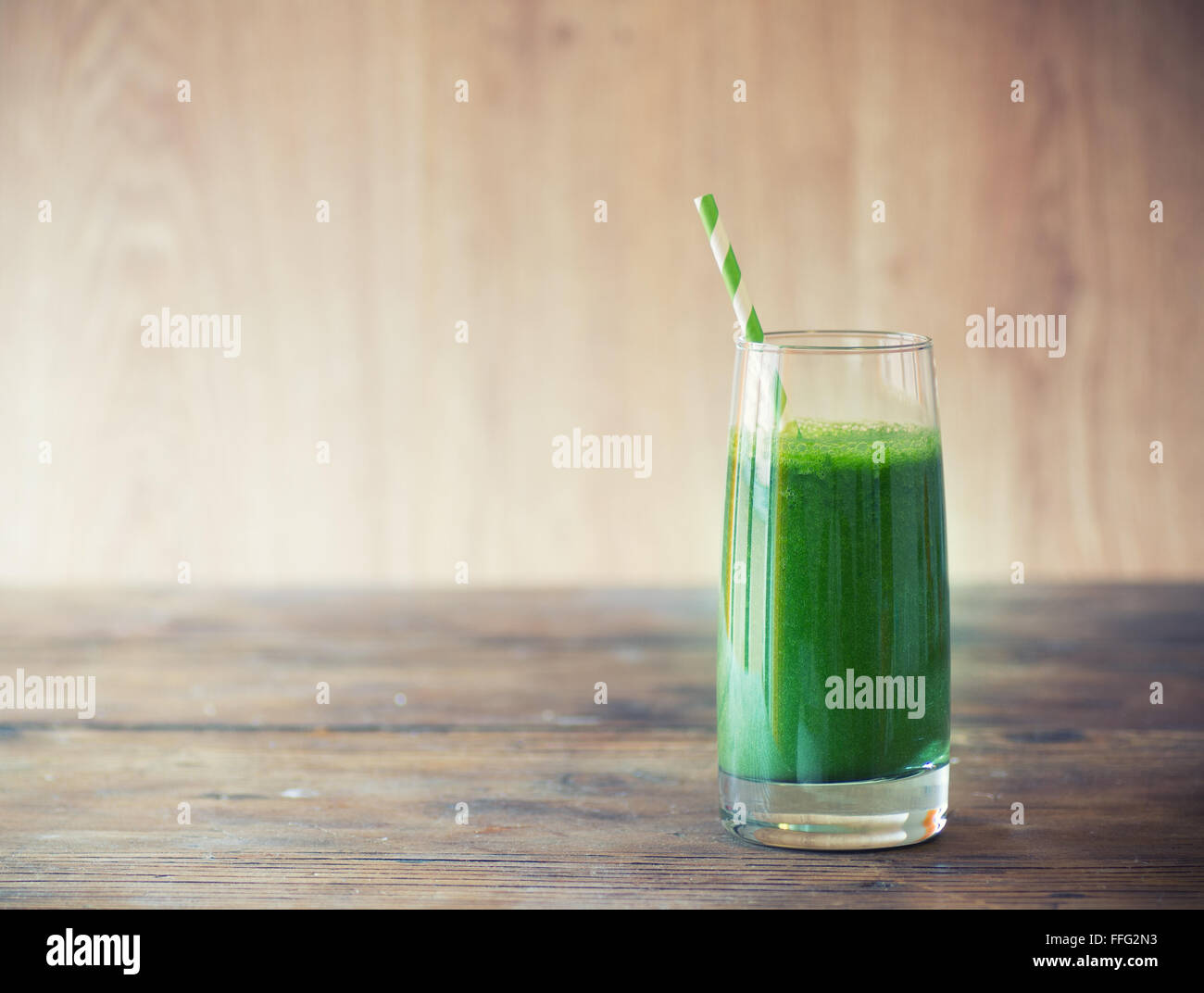 Green smoothie on vintage wooden background - Stock Image
