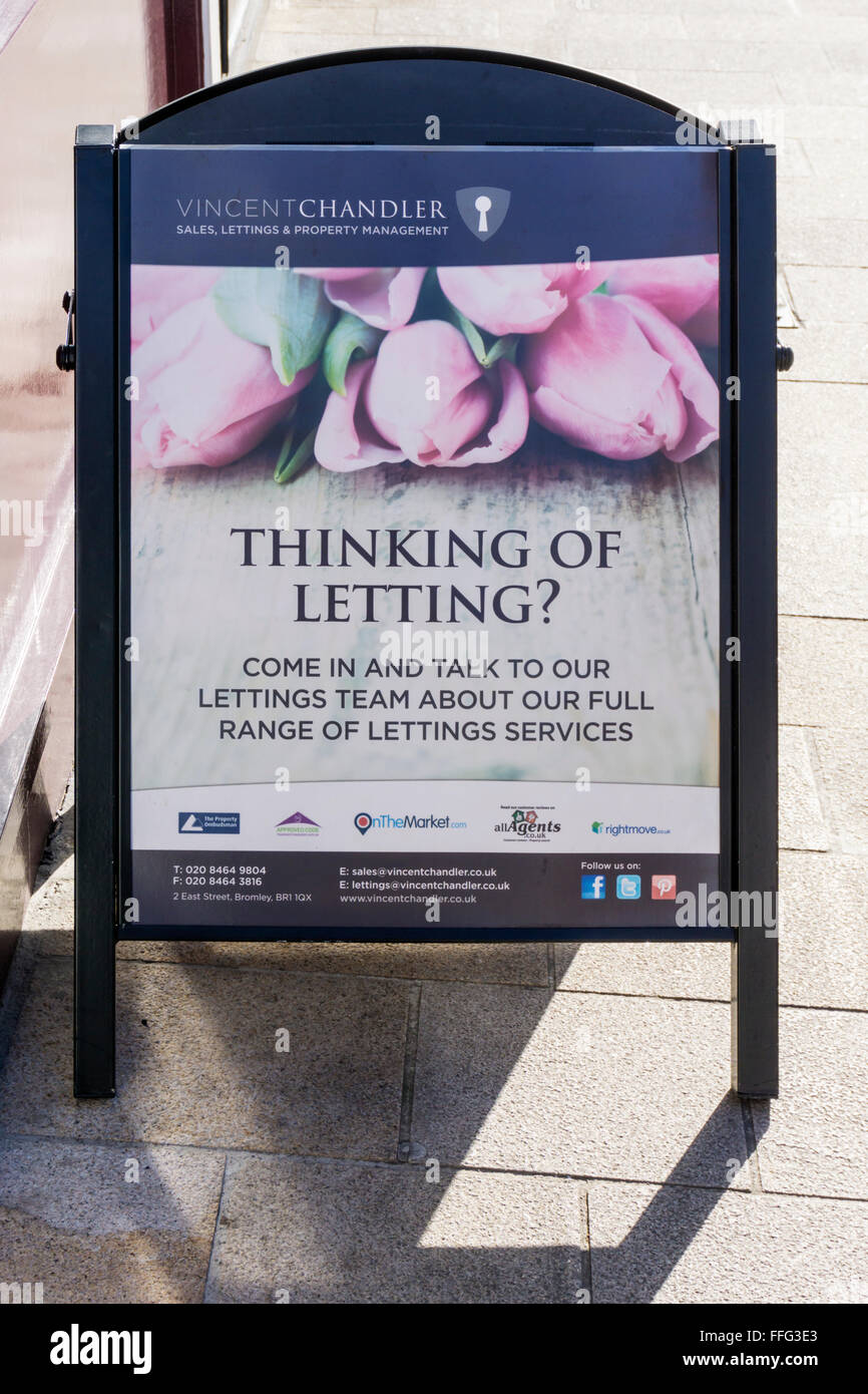 A sign outside an estate agents advertises letting services. - Stock Image