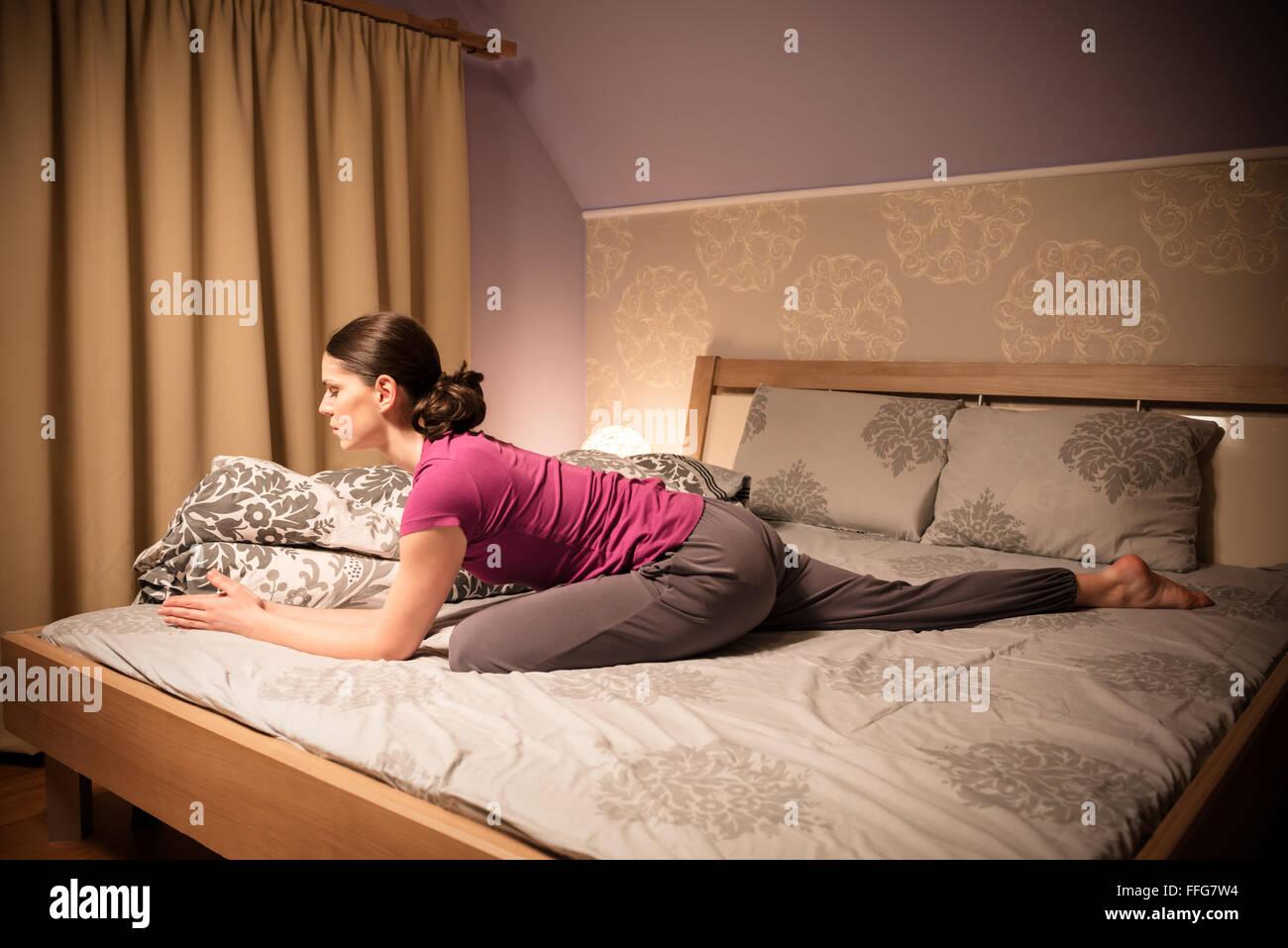 Young woman doing the Pigeon yoga pose before going to sleep. - Stock Image