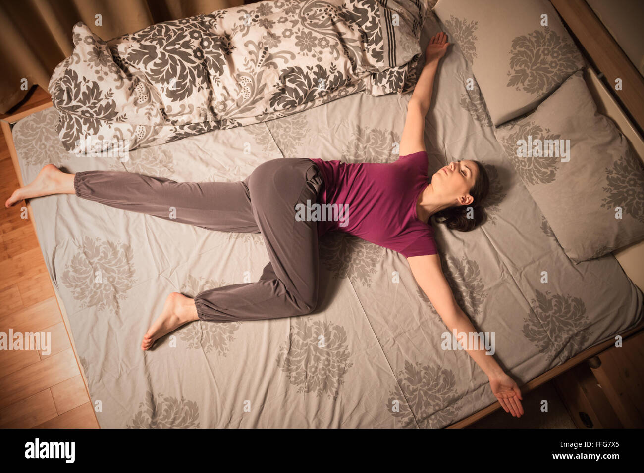 Young woman doing the Reclining Spinal Twist yoga pose before going to sleep. - Stock Image