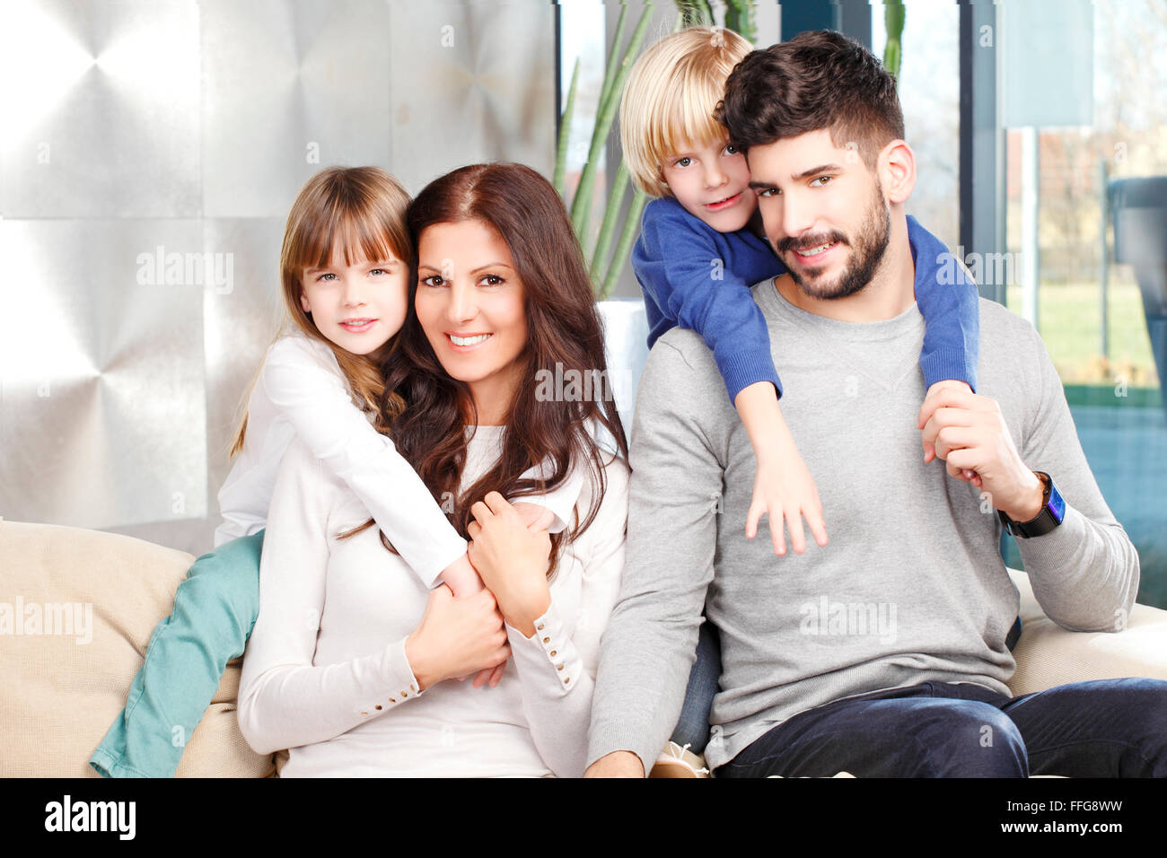 Portrait of happy young family with two kids sitting at sofa and smilig. Happy father giving piggyback to his cute - Stock Image