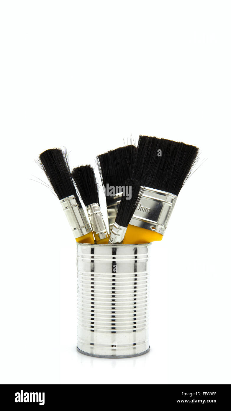 New Paint Brushes in a tin on a white background - Stock Image