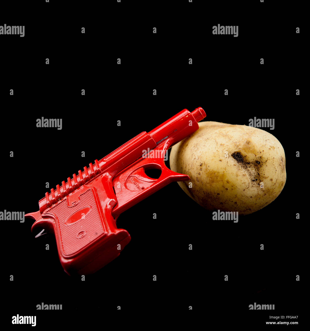 Spud Gun with potato on Black Background - Stock Image
