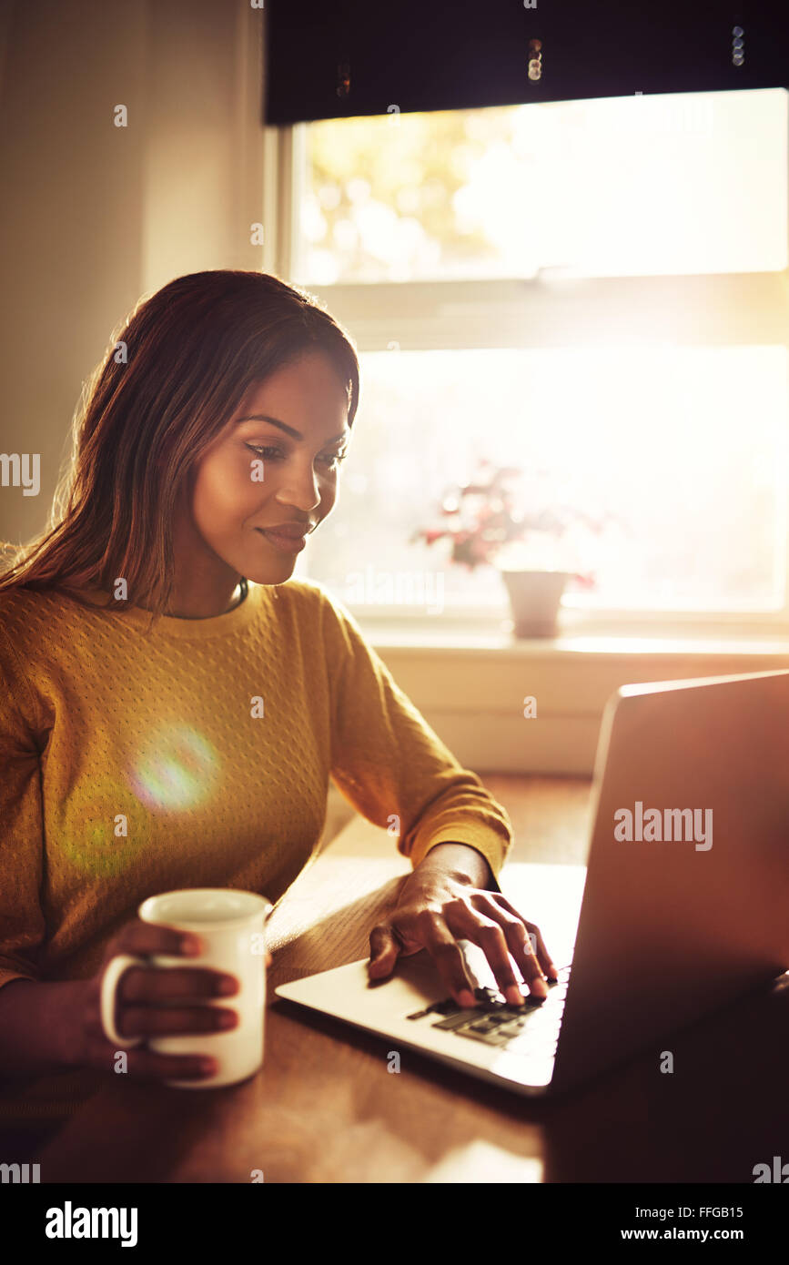 Happy gorgeous adult single female sitting near bright sunny window typing on her laptop computer and holding coffee - Stock Image