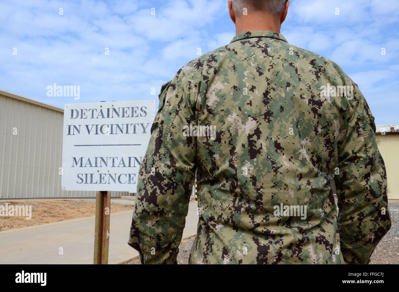 guantanamo bay cuba gtmo camp delta detainees in vicinity maintain silence sign with soldier - Stock Image