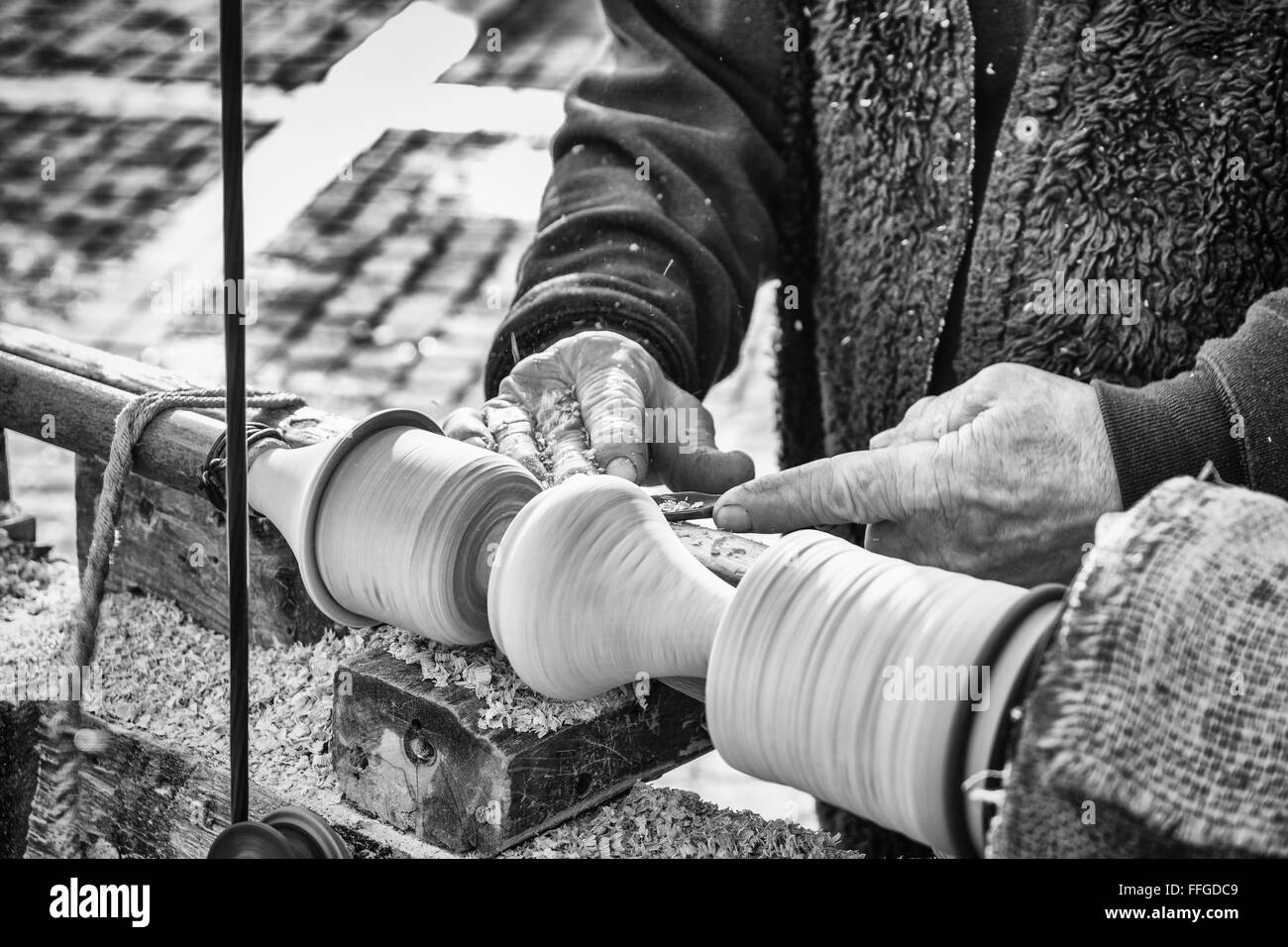 An artisan carves a piece of wood using an old manual lathe. - Stock Image