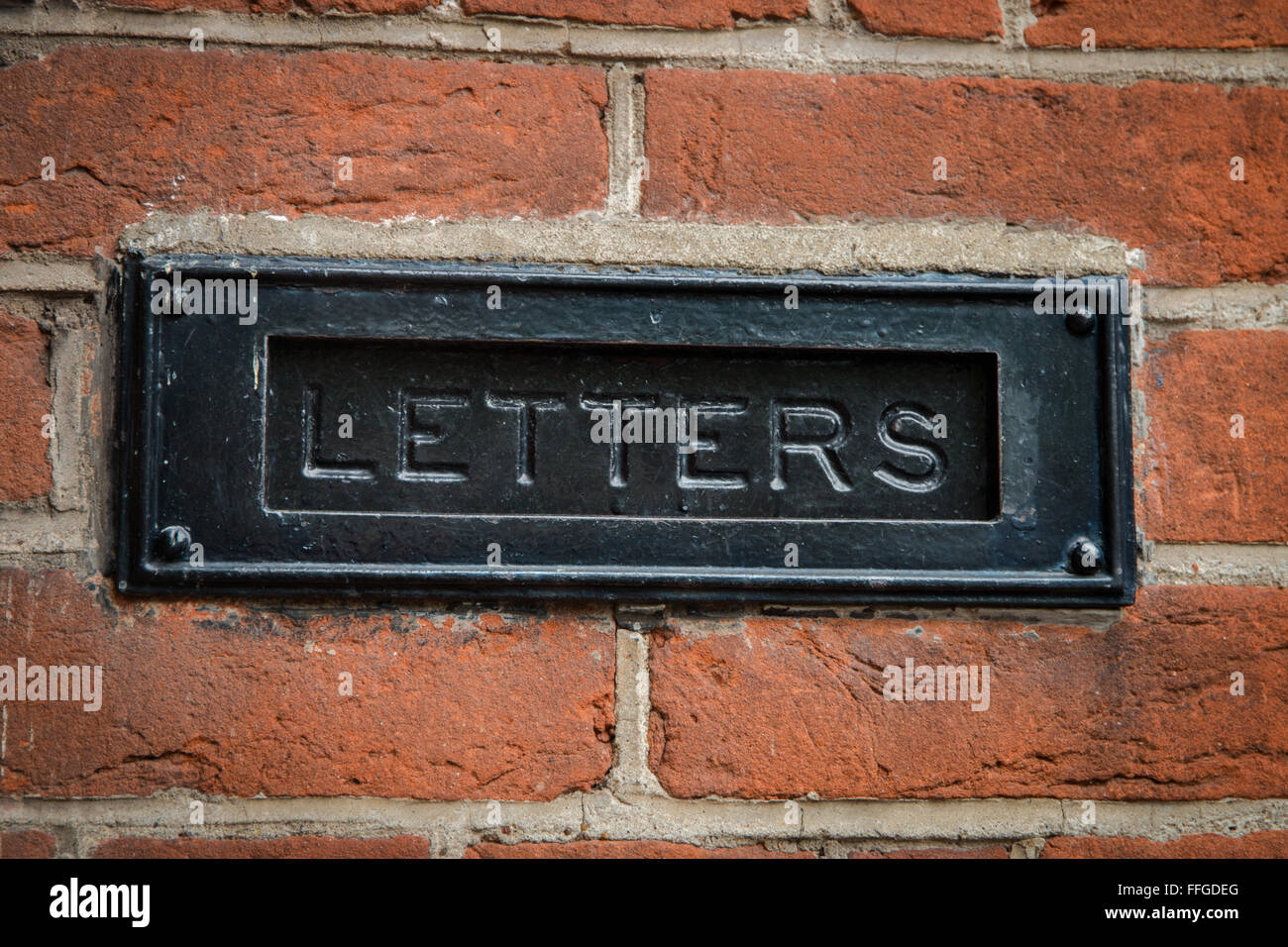 A letter box set in a brick wall engraved with the word 'letters' - Stock Image
