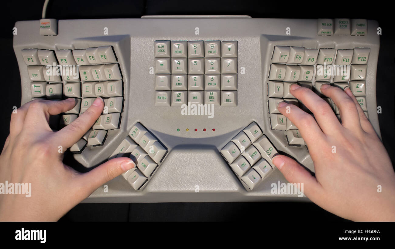Hands typing on a ergonomic 'split keyboard' designed to avoid repetitive strain injury. - Stock Image
