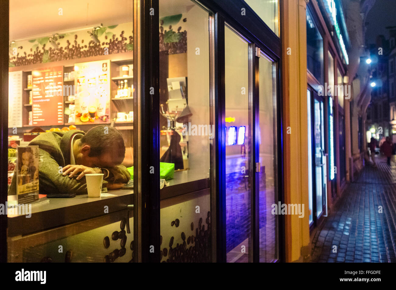 Lonely man falling asleep at a cafe at night as seen from the street - Stock Image