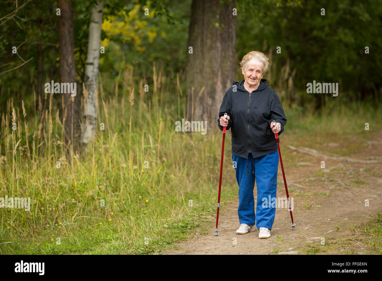 Elderly woman engaged in Nordic walking in the Park. - Stock Image