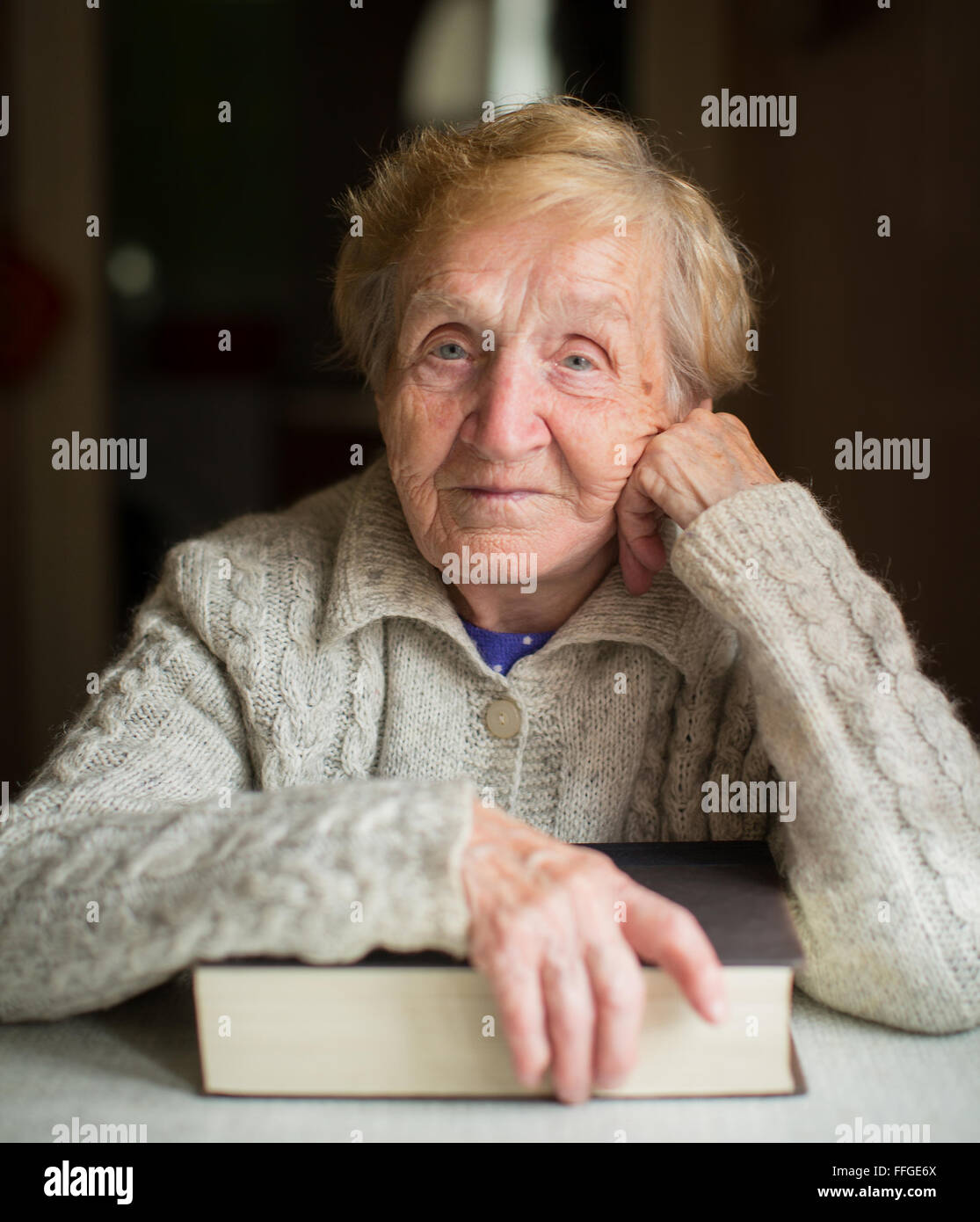 Portrait of elderly woman sitting with book. - Stock Image