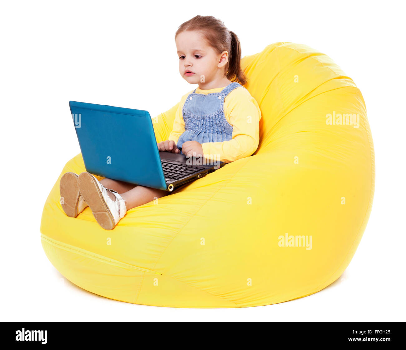 Child  sitting on a bean bag with laptop - Stock Image - Stock Image