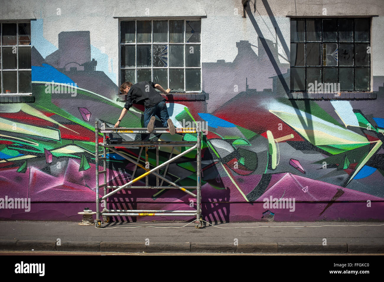 Street artist painting on a sunny afternoon, Stokes Croft, Bristol, England - Stock Image