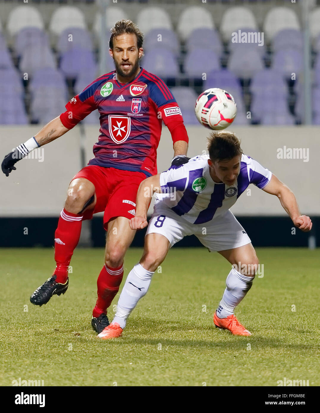 Budapest, Hungary. 13th Feb, 2016. Balazs Balogh of Ujpest (r) heads on target next to Andras Fejes of Videoton - Stock Image