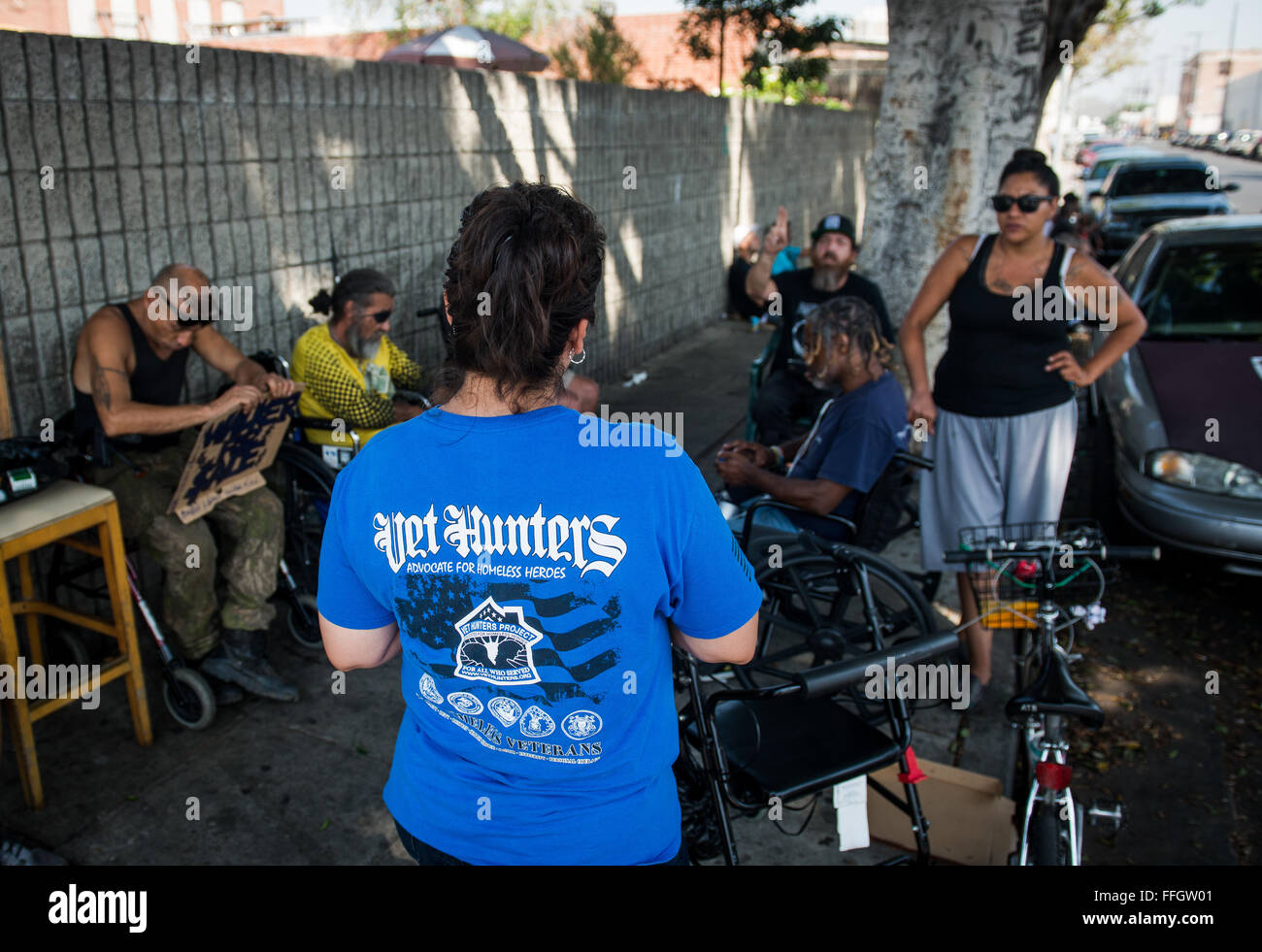 Vet Hunter Mayra Galicia talks to a small group of homeless individuals on Skid Row to see if they're veterans - Stock Image