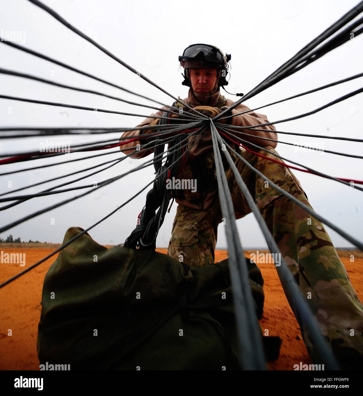 Senior Airman Oren Palmer with the 21st Special Tactics Squadron, pulls in his parachute after a jump at Pope Field, - Stock Image