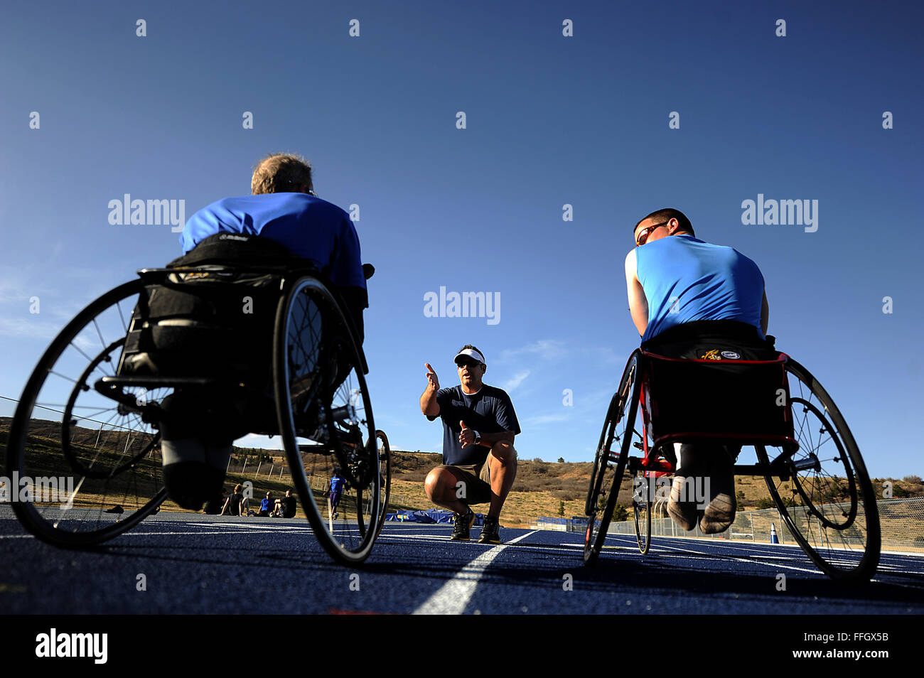 Former Senior Airman Jeff Odom listens to his coach before racing laps in his race chair at the Air Force team's - Stock Image
