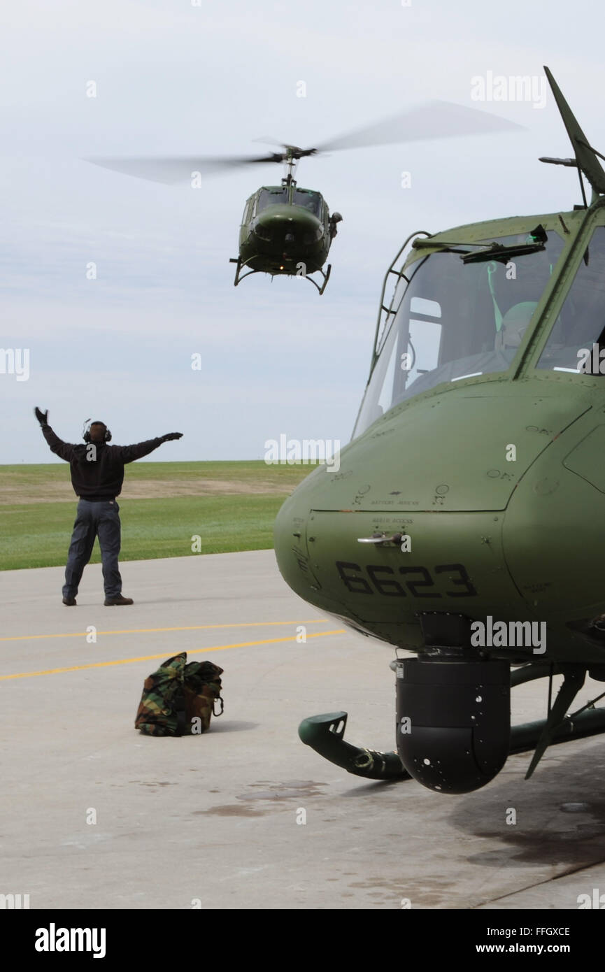 A mechanic from the 54th Helicopter Squadron guides a UH-1N Huey to the landing pad at Minot Air Force Base, N.D. Stock Photo