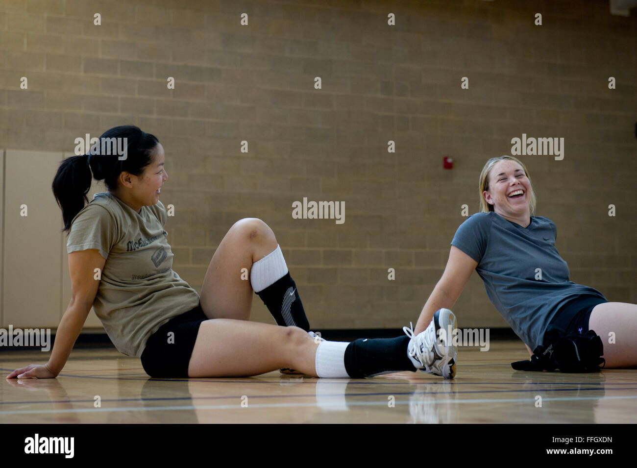 Capt. Sally To (left) and Airman 1st Class Kristina Englebert, talk and stretch after volleyball practice at Hill - Stock Image