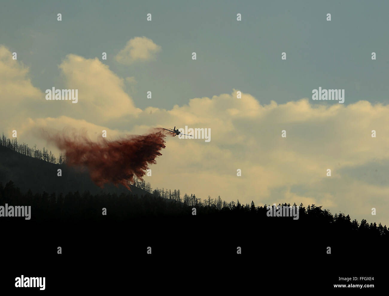 A small prop plane drops fire retardent  on the fire as firefighters continued to battle the blaze that burned into - Stock Image