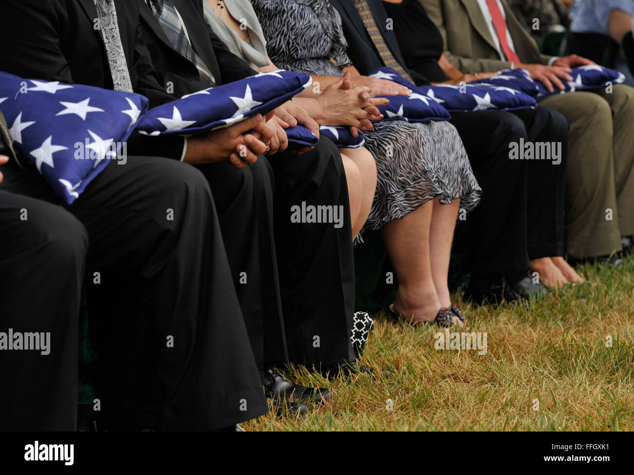 Family members of six fallen Airmen hold the folded flags they received during a funeral service at Arlington National - Stock Image