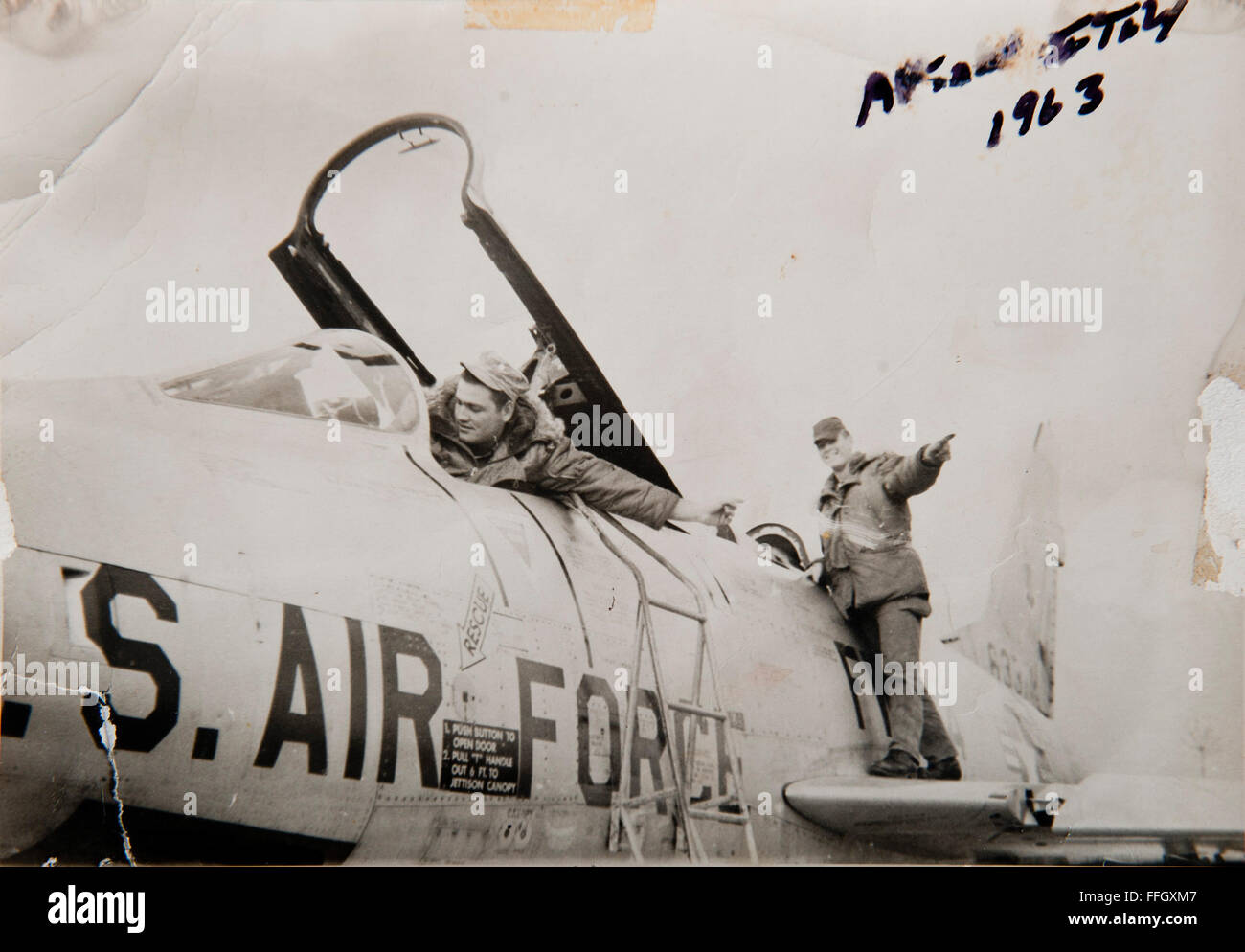 Hackworth (left) performs a flight control check on an F-100 Super Sabre with Airman Richard Evinasky in 1963 at - Stock Image