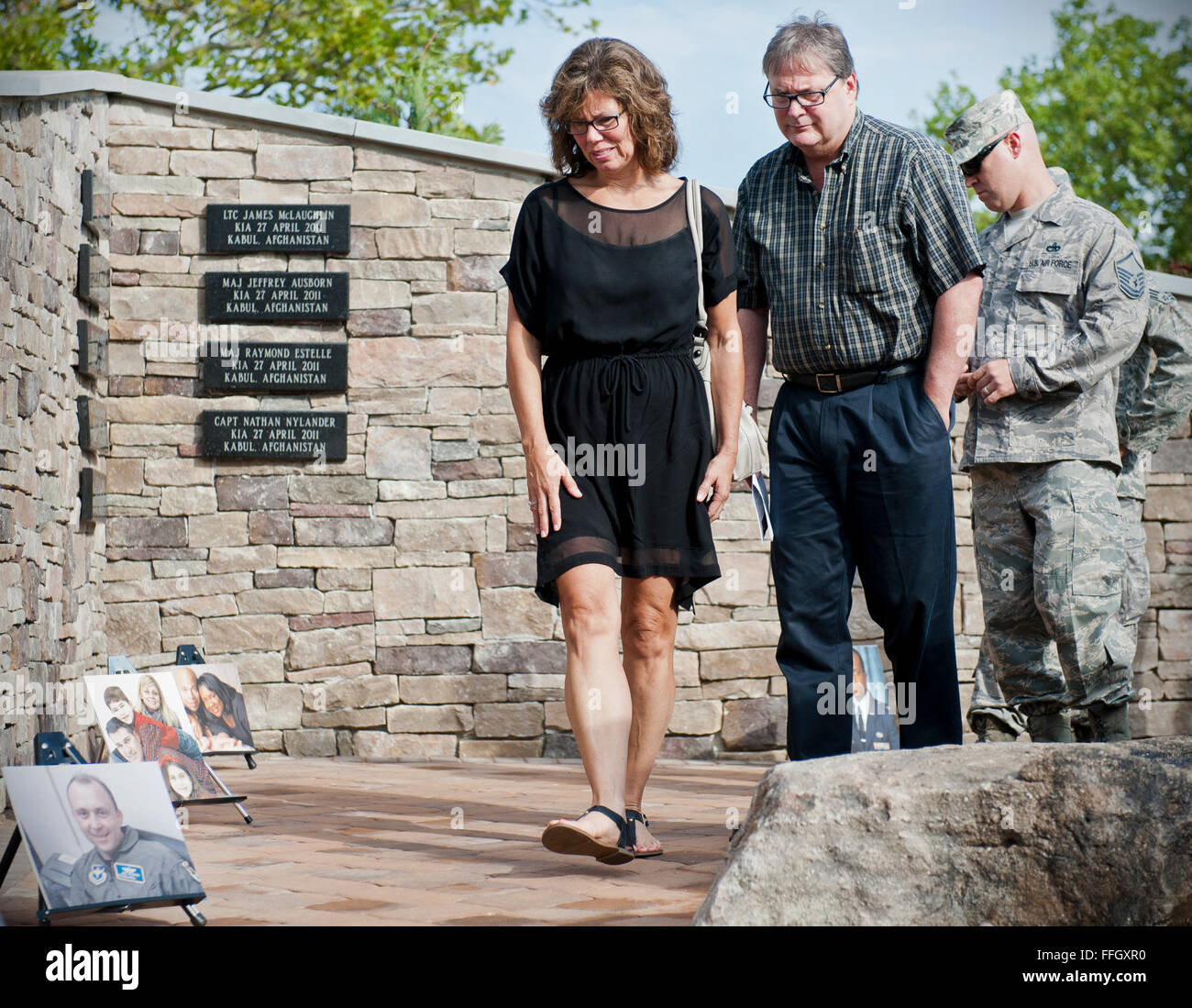 Family and friends look at plaques and photos of the nine fallen air advisors before the memorial dedication ceremony. - Stock Image