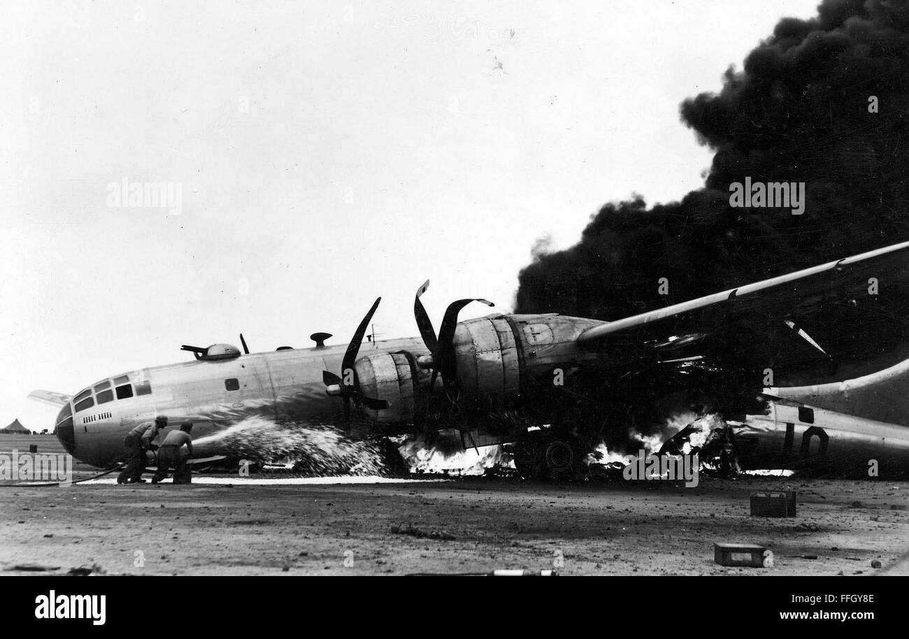 Smoke billows from a B-29 Stratofortress after the aircraft made an emergency landing on Iwo Jima. - Stock Image