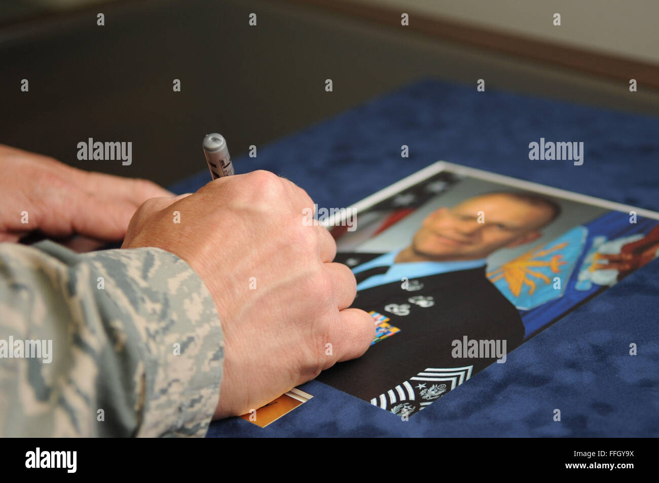 Chief Master Sgt. of the Air Force James A. Roy signs an official photograph of himself for the Pitsenbarger Airman - Stock Image